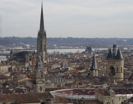 Vue d'une partie du secteur sauvegardé de Bordeaux depuis les toits. Garonne et flèche Saint-Michel en arrière plan. Toit du Palais des Sports au premier plan. Grosse cloche, monuments historiques et immeubles d'habitation.
