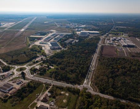 Vue arienne sur le boulevard Dassault avec de part et d'autres les pistes et des entreprises implantées au milieu d'une végétation dense