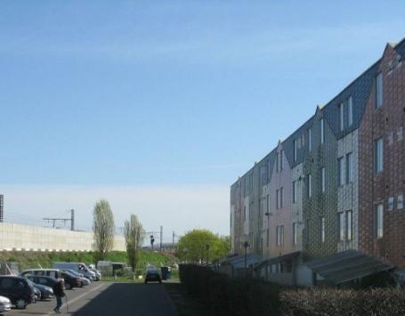 Au premier plan, la résidence les Erables. Au second plan, le mur et les caténaires de la voie ferrée.